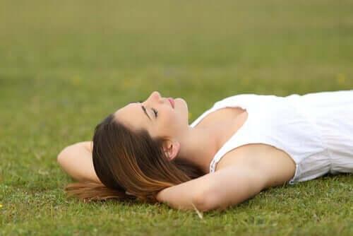 Een vrouw ligt ontspannen in het gras