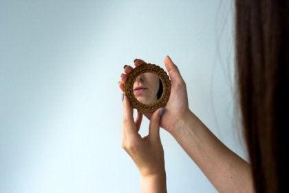 Vrouw kijkt naar eigen spiegelbeeld