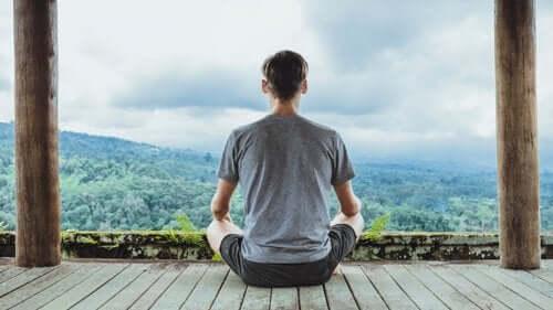 Een man mediteert en kijkt uit over bergen