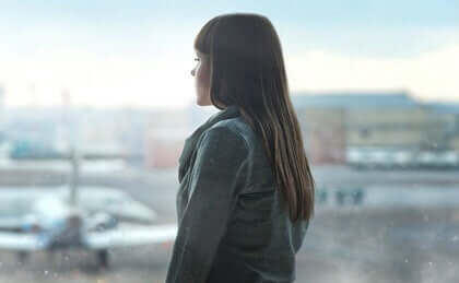 Een vrouw staart uit het raam
