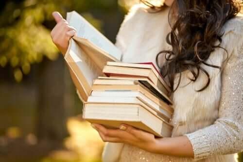 Een vrouw met een stapel boeken