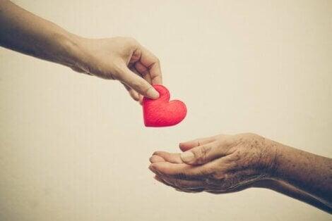 Een jongere hand geeft een oudere hand een hartje