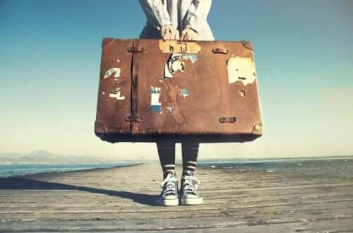Een vrouw houdt een grote koffer vast