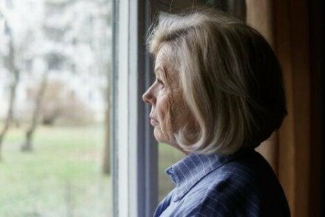 Een oudere vrouw kijkt uit het raam