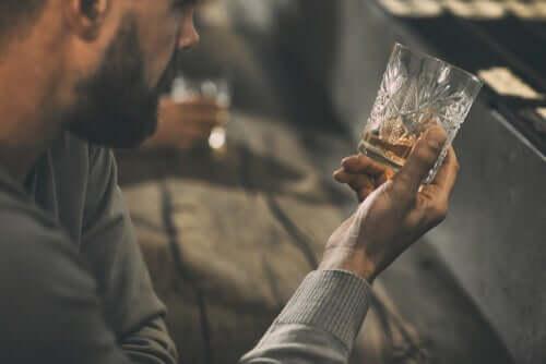 Een man kijkt naar een bijna leeg glas alcohol