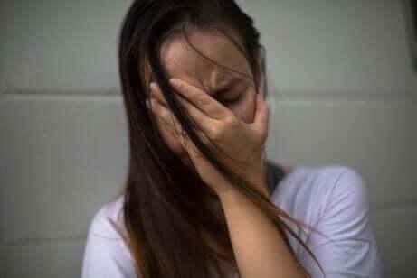 Een bange vrouw met haar hand voor haar gezicht