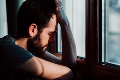 Een angstige man zit bij het raam