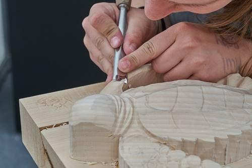 Een vrouw maakt een schildpad van hout