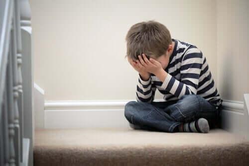 Een verdrietig jongetje met zijn handen voor zijn gezicht