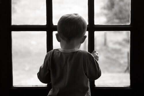 Een jongetje kijkt uit een raam