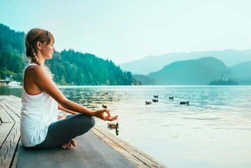 Een vrouw mediteert aan een meer
