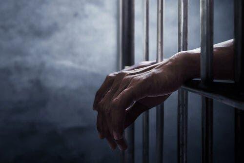 Twee handen steken door de tralies van een gevangenis