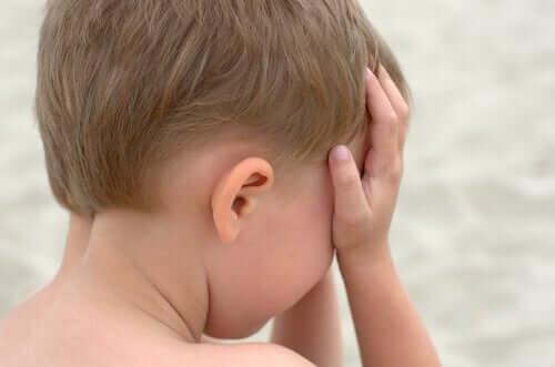 Een huilend kind met zijn handen voor zijn gezicht