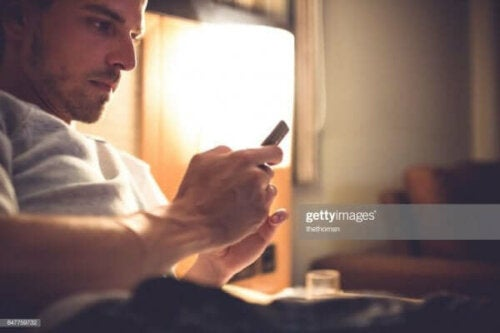 Een man kijkt op zijn mobiele telefoon