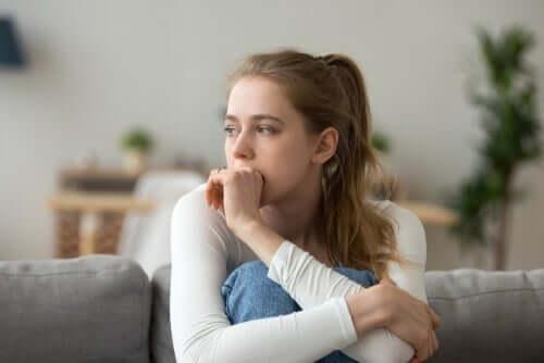 Een vrouw zit op de bank met haar knieën opgetrokken