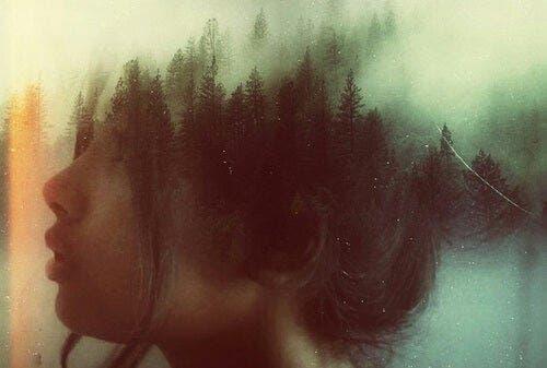 Een vrouw met de reflectie van een bos over haar hoofd