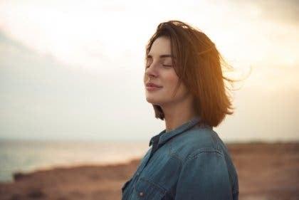 Een vrouw sluit haar ogen en staat op het strand