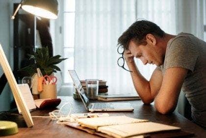 Een vermoeide man zit aan zijn bureau