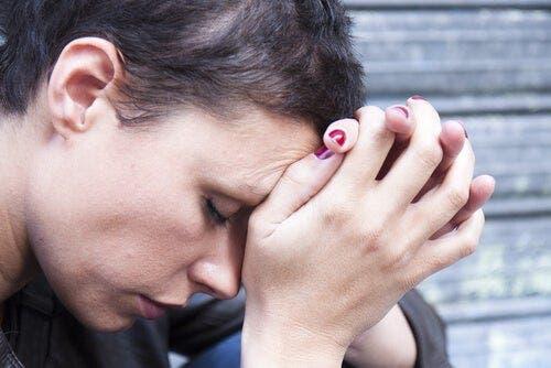 Een vrouw houdt haar handen tegen haar voorhoofd