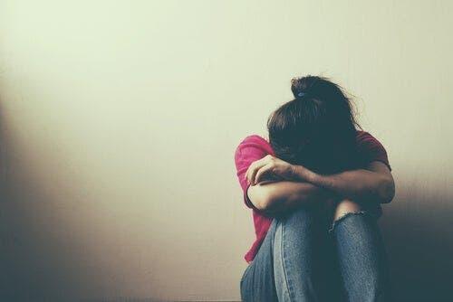 Een meisje zit huilend tegen de muur