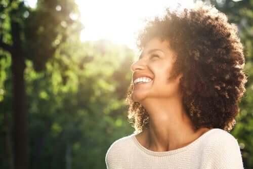 Lachende vrouw met bomen op de achtergrond