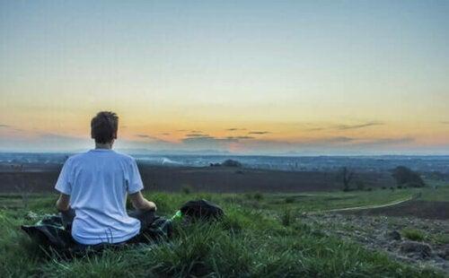 Een man mediteert in de buitenlucht