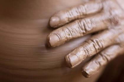 Een hand die klei aanraakt