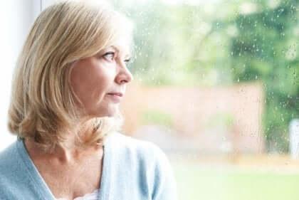 Een vrouw kijkt nadenkend uit het raam