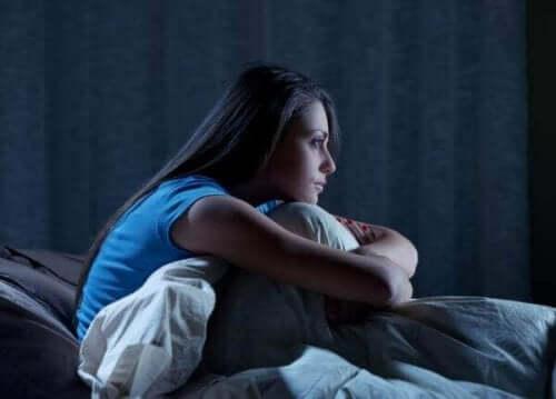 Een vrouw zit in het donker rechtop in bed