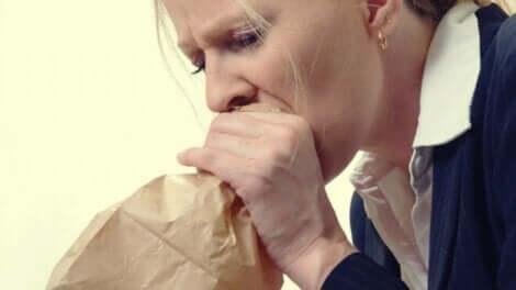 Vrouw blaast in zak om ademhaling te regelen