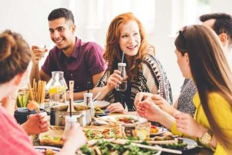 Een groep mensen zit aan tafel te eten en te praten