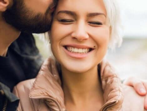 Een man kust een vrouw op de wang