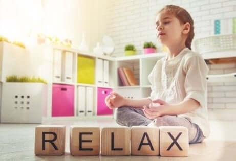 Het woord relax uitgespeld in houten blokken met een kind in meditatiehouding
