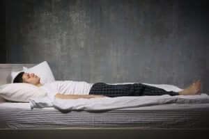 Een man ligt in bed met zijn ogen dicht