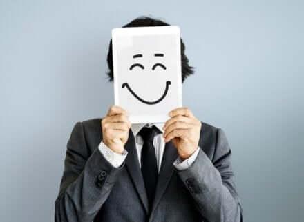 Een man houdt een vel papier met een lachend gezicht voor zijn eigen gezicht