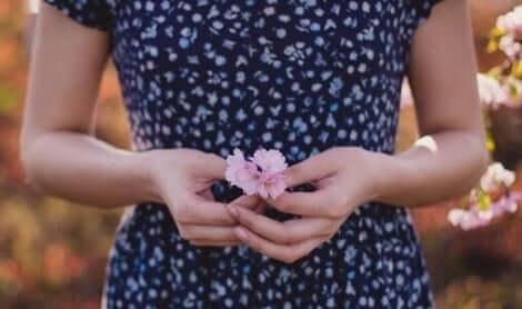 Een vrouw houdt een roze bloem in haar handen