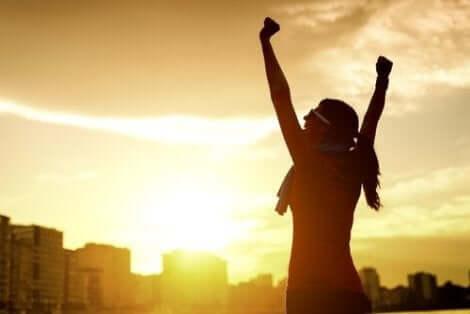 Een vrouw steekt juichend haar armen in de lucht