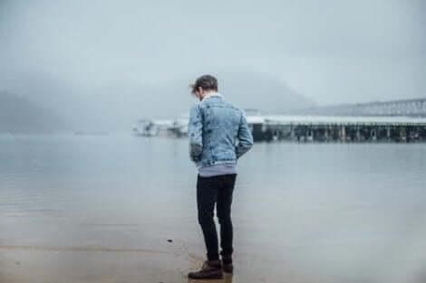 Een man staat eenzaam op het strand