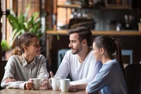 Drie mensen met elkaar in gesprek in een café
