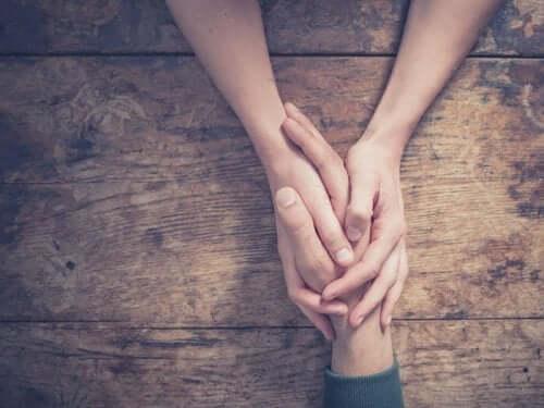 Een vrouw houdt de hand van een man vast boven een tafel