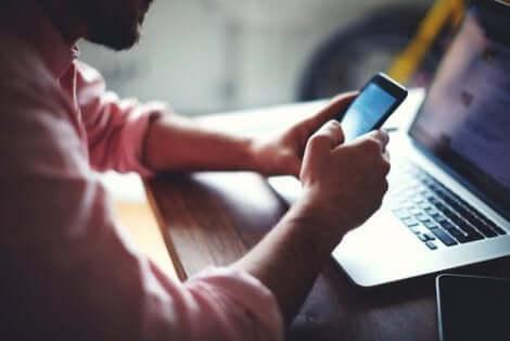 Een man kijkt op zijn telefoon terwijl hij op zijn laptop bezig is