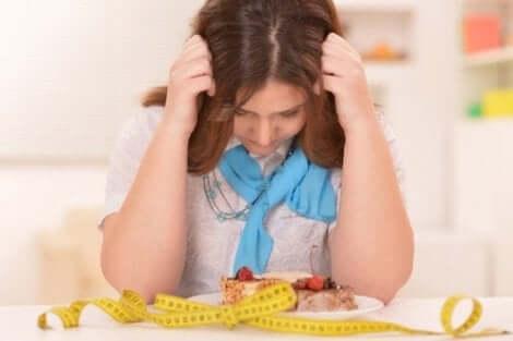 Een vrouw zit met haar handen in het haar boven een bord eten en een meetlint