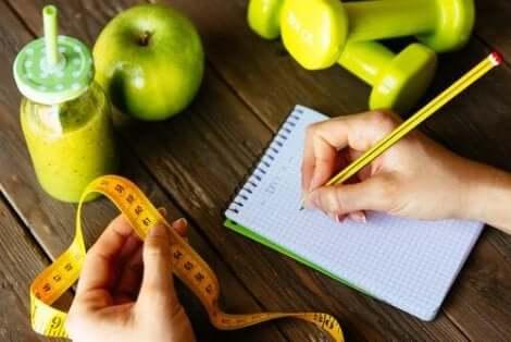 Een vrouw noteert haar omvang in een notitieboekje