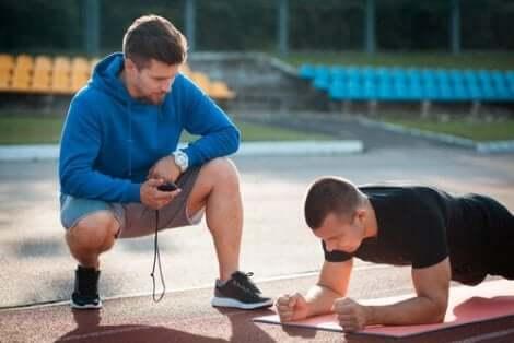 Een trainer kijkt toe hoe een sporter zich opdrukt