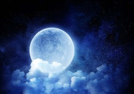 Een volle maan achter de wolken