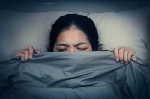 Een vrouw trekt de deken op tot haar kin