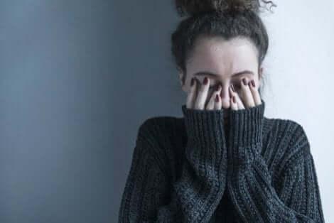 Een vrouw houdt haar handen voor haar gezicht