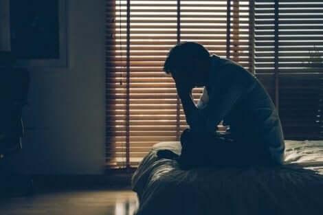 Een man zit op de rand van zijn bed met zijn handen voor zijn gezicht