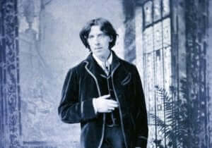 Oscar Wilde in een zwartwit foto met zijn hand op zijn buik