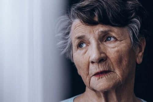 Een oudere vrouw staat naast het raam